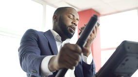 Entrenamiento cansado del hombre de negocios en la bici inmóvil y el hablar en smartphone en el gimnasio almacen de video