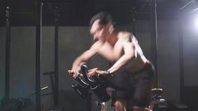 Entrenamiento cardiio Entrenamiento atlético descamisado del hombre en la máquina de ciclo en gimnasio almacen de video