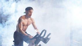 Entrenamiento cardiio Entrenamiento atl?tico descamisado del hombre en la m?quina de ciclo en gimnasio almacen de metraje de vídeo