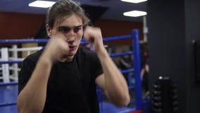Entrenamiento caucásico joven del hombre en el ring de boxeo en gimnasio moderno Luchar la sombra Kickboxer en camiseta negra y p almacen de video