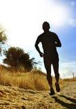 Entrenamiento corriente del campo a través de la silueta del hombre joven delantero del deporte en la puesta del sol del verano Foto de archivo libre de regalías