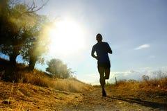 Entrenamiento corriente del campo a través de la silueta del hombre joven delantero del deporte en la puesta del sol del verano Fotografía de archivo libre de regalías