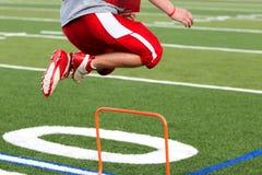 Entrenamiento cruzado del futbolista sobre mini obstáculos anaranjados Fotografía de archivo libre de regalías