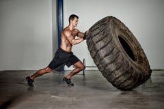 Entrenamiento de Crossfit - hombre que mueve de un tirón el neumático foto de archivo