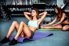 Entrenamiento de dos chicas jóvenes en el gimnasio Foto de archivo libre de regalías
