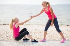 Entrenamiento de dos mujeres en la playa Foto de archivo libre de regalías