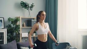Entrenamiento de elevación del peso de la muchacha muscular con pesas de gimnasia en el plano centrado en práctica almacen de video