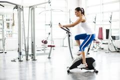 Entrenamiento de giro del ejercicio de la mujer de los aeróbicos en el gimnasio de las bicis Imagen de archivo libre de regalías