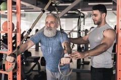 Entrenamiento de goce masculino mayor confiado con el instructor en centro atlético Fotografía de archivo