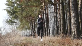 Entrenamiento de la aptitud al aire libre Mujer del deporte que corre a través del bosque almacen de video
