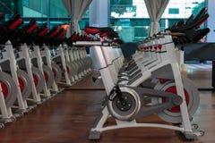 Entrenamiento de la aptitud en gimnasio: Grupo de bicis de giro modernas en línea Fotografía de archivo libre de regalías