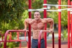 Entrenamiento de la calle - entrenamiento muscular hermoso del hombre en el parque imagen de archivo