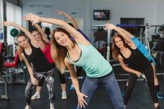 Entrenamiento de la conducta de las muchachas en aptitud en el gimnasio Imagen de archivo libre de regalías