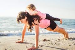 Entrenamiento de la familia - madre e hija que hacen ejercicios en la playa Imágenes de archivo libres de regalías