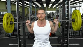 Entrenamiento de la fuerza en el gimnasio individuo en la camiseta que hace posiciones en cuclillas con un barbell culturista que fotografía de archivo libre de regalías