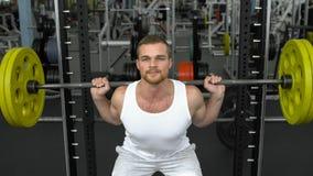 Entrenamiento de la fuerza en el gimnasio individuo en la camiseta que hace posiciones en cuclillas con un barbell culturista que imagenes de archivo