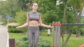 Entrenamiento de la mujer de la aptitud al aire libre con la cuerda que salta en parque del verano almacen de video