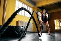 Entrenamiento de la mujer con las cuerdas de la batalla en gimnasio foto de archivo