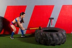 Entrenamiento de la mujer de golpes del neumático de la almádena en el gimnasio Imagen de archivo
