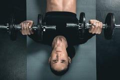 Entrenamiento de la mujer de la aptitud con pesas de gimnasia y mentira en la estera Fotos de archivo