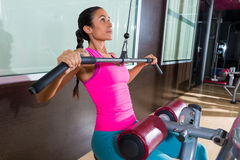 Entrenamiento de la mujer de la máquina de la desconexión del lat en el gimnasio Fotos de archivo