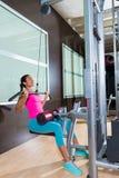 Entrenamiento de la mujer de la máquina de la desconexión del lat en el gimnasio Imagenes de archivo