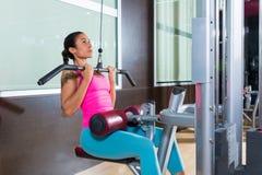Entrenamiento de la mujer de la máquina de la desconexión del lat en el gimnasio Fotos de archivo libres de regalías
