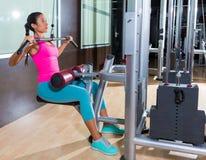 Entrenamiento de la mujer de la máquina de la desconexión del lat en el gimnasio Imagen de archivo libre de regalías