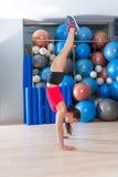 Entrenamiento de la mujer de la posición del pino en las bolas del gimnasio y del suizo Foto de archivo