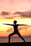 Entrenamiento de la mujer de la yoga y el meditar en actitud del guerrero Imagen de archivo