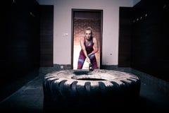 Entrenamiento de la mujer del martillo de trineo de la aptitud en el gimnasio El entrenamiento de la mujer de golpes del neumátic fotos de archivo libres de regalías