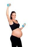 Entrenamiento de la mujer embarazada de la morenita con pesas de gimnasia Imagen de archivo