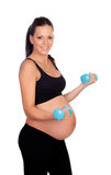 Entrenamiento de la mujer embarazada de la morenita con pesas de gimnasia Fotografía de archivo libre de regalías