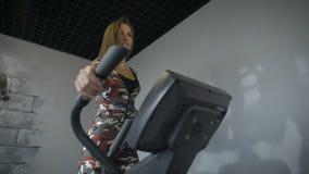 Entrenamiento de la mujer en un instructor cruzado en el gimnasio almacen de metraje de vídeo