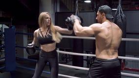Entrenamiento de la mujer joven con el coche en club del boxeo almacen de metraje de vídeo