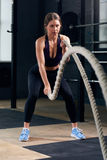 Entrenamiento de la mujer joven con las cuerdas de la batalla en gimnasio foto de archivo