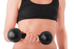 Entrenamiento de la mujer joven con pesas de gimnasia Imagenes de archivo