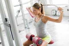 Entrenamiento de la mujer joven en el gimnasio Fotografía de archivo libre de regalías