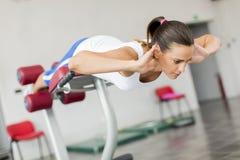 Entrenamiento de la mujer joven en el gimnasio Foto de archivo libre de regalías