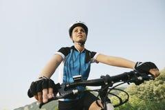 Entrenamiento de la mujer joven en la bici de montaña y ciclo en parque Imagen de archivo libre de regalías