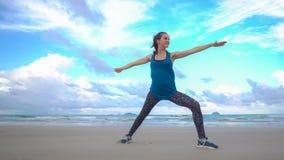 Entrenamiento de la mujer joven en la playa delante del mar Ejercicios gimnásticos de la mañana Concepto activo sano de la forma  Fotografía de archivo libre de regalías