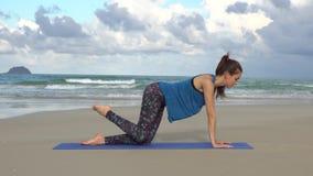 Entrenamiento de la mujer joven en la playa delante del mar Mañana gimnástica Ejercicio de pierna Concepto activo sano de la form almacen de video