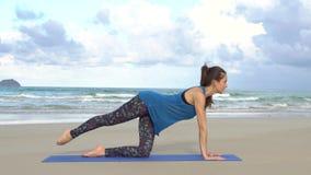Entrenamiento de la mujer joven en la playa delante del mar Mañana gimnástica Ejercicio de pierna Concepto activo sano de la form metrajes