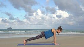 Entrenamiento de la mujer joven en la playa delante del mar Mañana gimnástica Ejercicio del tablón Concepto activo sano de la for metrajes