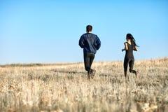 Entrenamiento de la mujer y del hombre en el campo, activando detrás la visión Fotografía de archivo