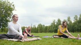 Entrenamiento de la yoga en parque - los deportistas jovenes realizan el ejercicio de la flexibilidad al aire libre metrajes