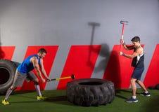 Entrenamiento de los hombres de golpes del neumático de la almádena en el gimnasio Imagen de archivo libre de regalías