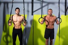 Entrenamiento de los hombres del anillo dos de la inmersión de Crossfit en el gimnasio Foto de archivo