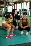 Entrenamiento de los pares de la aptitud - el hombre y la mujer aptos entrenan en gimnasio Fotografía de archivo libre de regalías