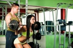 Entrenamiento de los pares de la aptitud - mann y la mujer aptos entrenan en gimnasio Fotografía de archivo libre de regalías